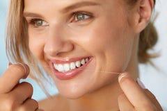 Saúde dental Mulher com o sorriso bonito que Flossing os dentes saudáveis imagem de stock