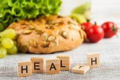 Saúde e bagel da palavra com salada imagem de stock