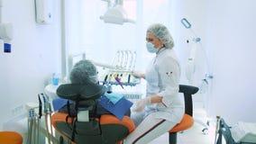 Saúde e cuidados dentários, mulher no trabalho como o dentista e doutor, falando a um paciente masculino Discuta o tratamento den filme