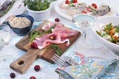 Sałatka garnela i warzywa w białym talerzu i szkle wino, mięso na drewnianej desce i kanapki, Fotografia Stock