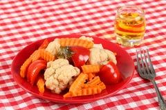 Sałatka kiszeni warzywa kalafior, papryka i marchwiani plasterki w czerwień talerzu i szkle rakia winogrono, brandy lubi obraz royalty free