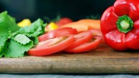 Sałatka liście, cutted pomidor, dzwonkowy pieprz i marchewka na drewnianej desce, robi zdrowej jarzynowej sałatki, dolly strzał zdjęcie wideo