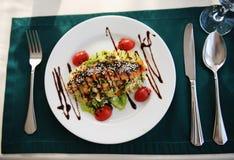 Sałatka z łososiem na białym talerzu Słuzyć na stole z zielonym tablecloth w restauraci Obraz Royalty Free