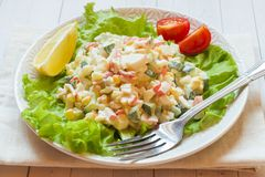 Sałatka z krabów kijami, słodką kukurudzą, ogórkiem, jajkami i majonezem na światło stole, obrazy stock