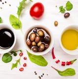 Sałatkowi opatrunki w białych pucharach z pikantność, oliwkami i dzikimi ziele, Zdjęcie Royalty Free