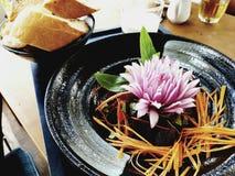 Sałatkowy naczynie z marchewka lampasami na czarnym talerzu z pięknym garnirunkiem, cebuli różą, liśćmi basil i baguette, obrazy royalty free