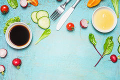 Sałatkowy przygotowanie z cutlery opatrunkowymi składnikami, sałatą, ziele i warzywami na bławym drewnianym tle, odgórny widok obraz royalty free
