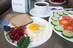 Sałatkowy talerz i rozdrapany jajko z filiżanki cofee na stole fotografia stock