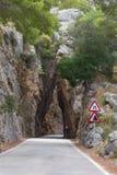 在山路的自然岩石隧道向Sa Calobra海滩,马略卡,西班牙 库存照片