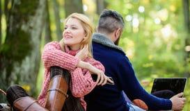 Sa?da de todas as contas Pares de amor felizes que relaxam no parque com dispositivos m?veis Apego do Internet Povos modernos foto de stock