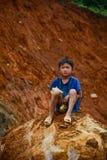 A boy sitting on rock Stock Photo