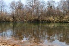 Saai bewolkt die de herfstlandschap, rivierbank en bomen in water wordt weerspiegeld Royalty-vrije Stock Afbeelding