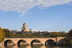 Saarbrucken Bridge with Sameba Cathedral in the background, in Tbilisi, Georgia. Saarbrucken Bridge over the River Mtkvari and Sameba Cathedral in Tbilisi Stock Images