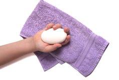 Sabão à disposição com toalha Fotografia de Stock Royalty Free