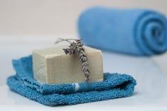 Sabão da alfazema na toalha de rosto e toalha azul rolada em t Imagem de Stock