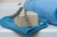 Sabão da alfazema na toalha de rosto e toalha azul rolada em t Foto de Stock Royalty Free