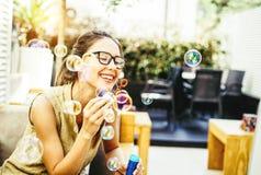 Sab?o de sopro das bolhas do partido da jovem mulher brincalh?o - et?reo no quintal - felicidade, alegria, conceito crian?ola da  foto de stock