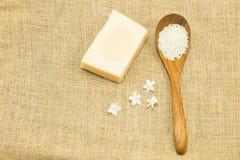 Sabão do leite do arroz ao lado do arroz do jasmim na colher de madeira no teste padrão do saco de gunny Foto de Stock Royalty Free