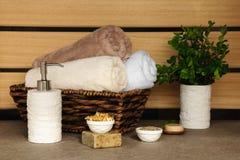 Sabão, ervas e toalhas em uma cesta de vime em um fundo claro Fotos de Stock Royalty Free
