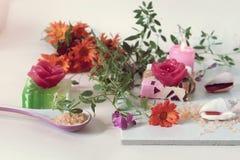 Sabão natural, velas, sal do mar, flores, escudos em um fundo claro fotografia de stock
