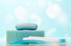 Sabão, pasta de dente e escova no banheiro no azul abstrato Imagens de Stock Royalty Free