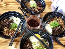 Sabah Chili Pan Mee Noodle. Four bowl of Sabah Chili Pan Mee noodle with four pairs of chopsticks on a wooden table. The food consist of noodle, egg, minced pork Royalty Free Stock Image