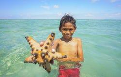 SABAH, MALAYSIA - NOVEMBER 19: Unidentified Bajau Laut kids hold a beautiful starfish at Maiga Island on November 19, 2015. Royalty Free Stock Photo
