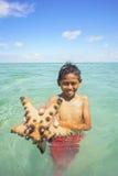 SABAH, MALAYSIA - NOVEMBER 19: Unidentified Bajau Laut kids hold a beautiful starfish at Maiga Island on November 19, 2015. Royalty Free Stock Image