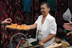 Sabantui celebration in Moscow. Woman offers traditional sweets to taste Stock Images