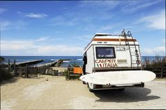 Sabaudia, Lazio, Italy - April 12, 2018: Rear of vintage camper parked on the beach seaside with a surfboard on back - Leisure. Rear of vintage camper parked on royalty free stock images