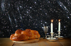 Sabbath image. challah bread and candelas on wooden table. glitter overlay Stock Photo