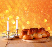 Sabbath image. challah bread and candelas on wooden table. glitter overlay.  Royalty Free Stock Images