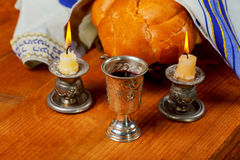 Sabbath image - Silver kiddush cup, crystal candlesticks with lit candles, and challah. Challahs Royalty Free Stock Photo