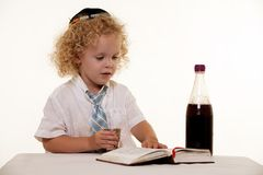 Sabbath ritual. Portrait of a curly hair blond little three year old boy wearing white shirt and tie and a kippah jewish hat practicing the Sabbath ritual Stock Photos