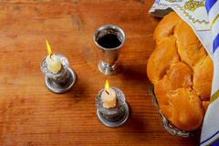 Sabbath Silver kiddush cup, crystal candlesticks with lit candles, and challah challahs. Sabbath image - Silver kiddush cup, crystal candlesticks with lit Royalty Free Stock Images