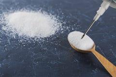 Sabbia bianca dello zucchero e siringa medica Danno di zucchero a salute fotografia stock libera da diritti