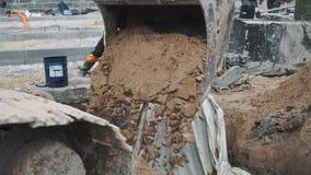 Sabbia cadente del secchio lento dell'escavatore in fossa al cantiere video d archivio
