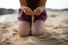 Sabbia cadente della ragazza di genuflessione da entrambe le mani fotografia stock libera da diritti