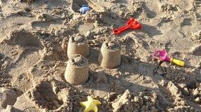 Sabbia, castelli e giocattoli immagine stock