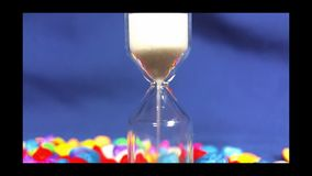 Sabbia che si esaurisce in clessidra su fondo blu stock footage