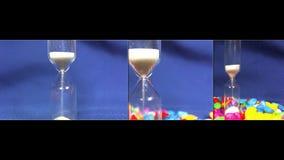 Sabbia che si esaurisce in clessidra su fondo blu archivi video