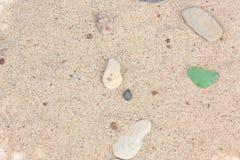 Sabbia con le pietre ed i pezzi di vetro Immagini Stock