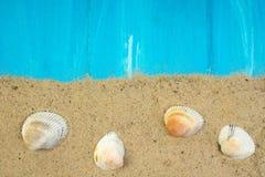 Sabbia, conchiglie, pietre su fondo blu Concetto della vista superiore di resto Fotografie Stock