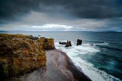 Sabbia del nero della costa dell'Islanda con il vento delle onde di oceano e il weathe tempestoso Immagini Stock