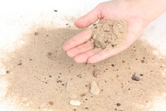 Sabbia della tenuta su fondo bianco Fotografia Stock