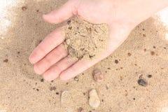 Sabbia della tenuta su fondo bianco Immagine Stock