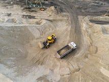 Sabbia di carico del grande caricatore pesante della ruota nell'autocarro con cassone ribaltabile nella cava di sabbia Concetto p fotografie stock
