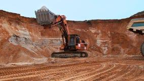 Sabbia di carico dell'escavatore nell'autocarro a cassone Suolo di scavatura dell'escavatore di Caterpillar video d archivio