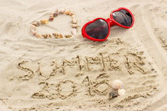 Sabbia di estate 2016 e cuore attinti delle coperture con gli occhiali da sole Fotografia Stock Libera da Diritti