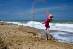 Sabbia di lancio della ragazza nell'aria Immagine Stock